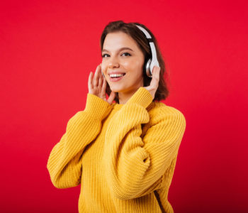Portrait of a smiling woman in headphones listening to music isolated over pink background